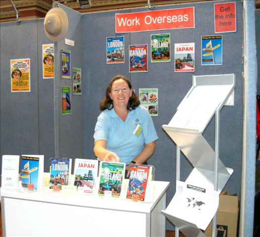 Sharyn McCullum surrounded by her Work Overseas travel guides at Melbourne's Backpacker Expo.