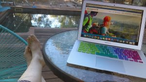 Sharyn McCullum Travel Writer sitting by her pool with her laptop.