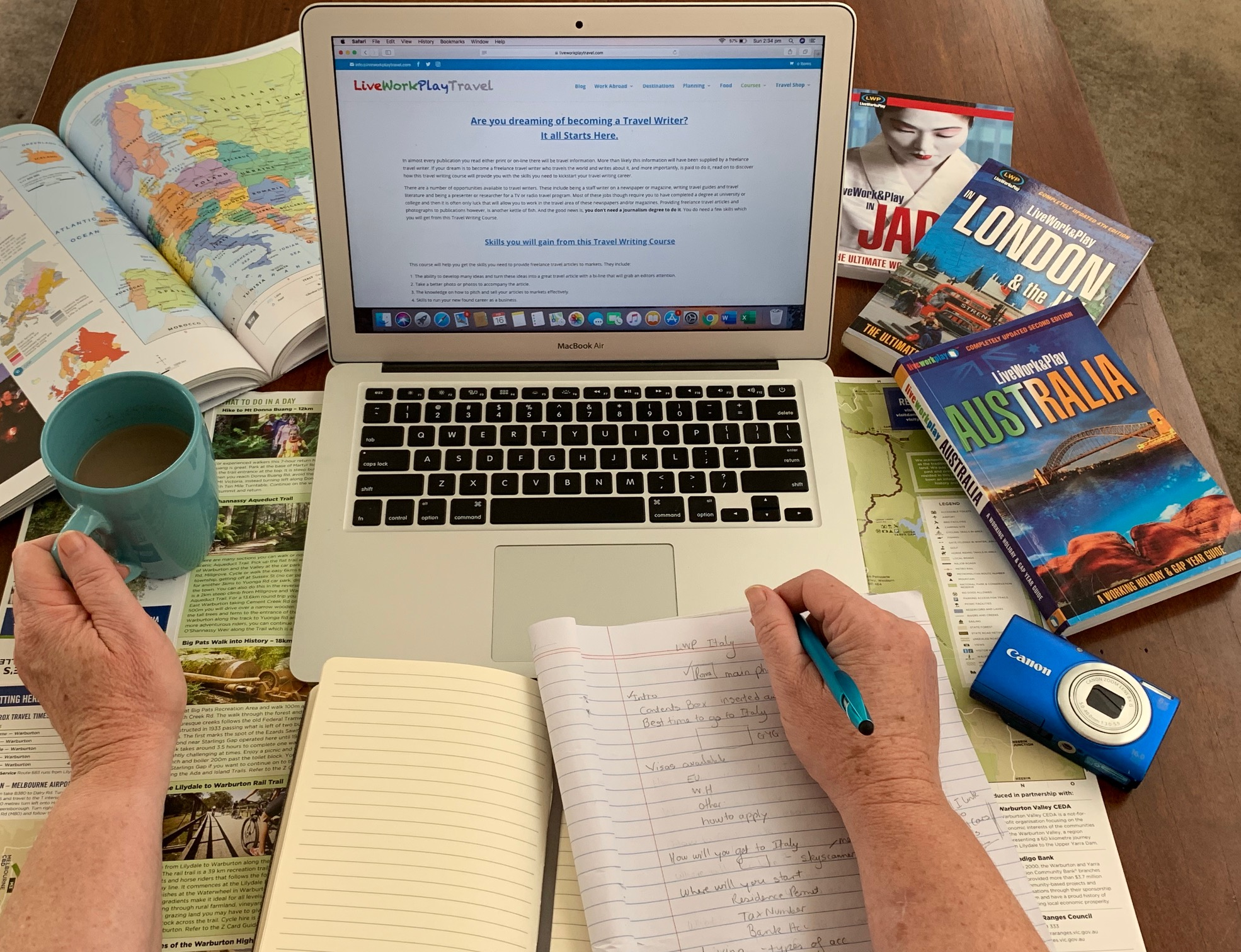 Laptop Of A Travel Writer Blogger With Books And A Coffee Cup.